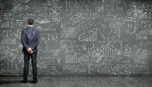 15597956-Business-person-standing-against-the-blackboard-with-a-lot-of-data-written-on-it-Stock-Photo