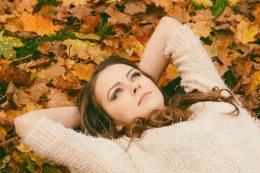 woman-in-sweater-laying-on-dried-maple-leaves-694445